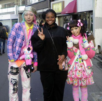 Asian Studies student abroad with colorfully dressed local street entertainers.