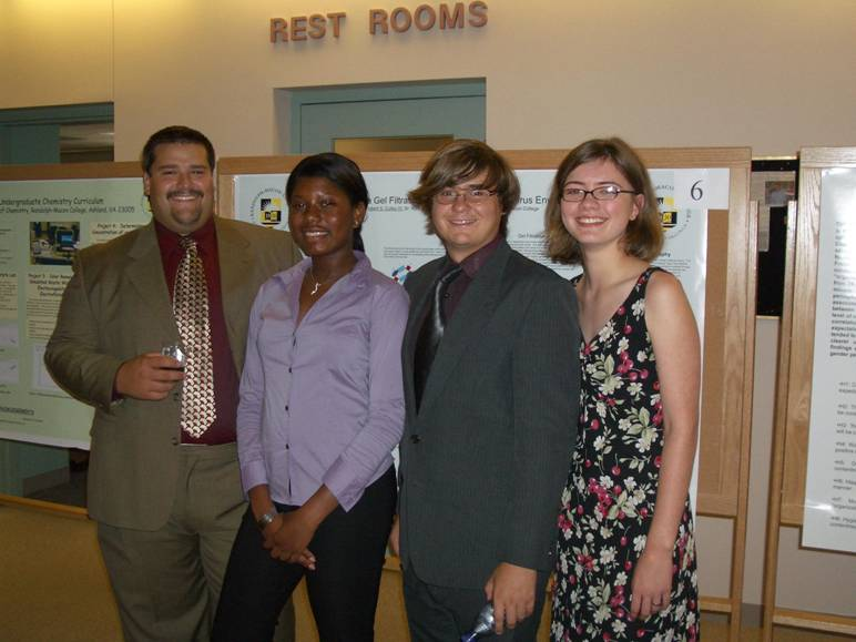 The Chemistry SURF fellow students dressed nicely, together in front of their posters at a conference.