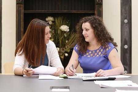two women discussing paperwork