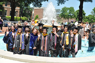 Large Group of Students in Graduation Robes Standing in Fountain