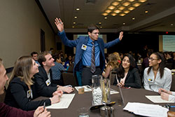 Student with Outstretched Arms Surrounded by Other Students in Presentation Area
