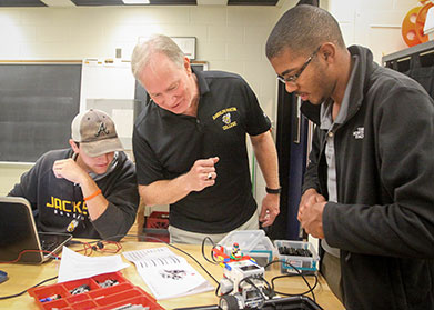 Professor and Two Students Examine Lego Robot