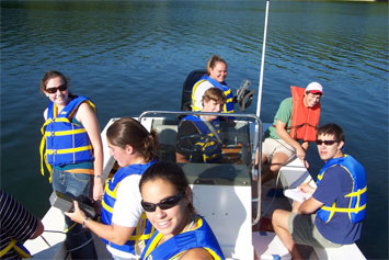 Students on a boat, wearing life-vests.