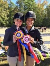Two Equestrian Team Members Displaying Winning Ribbons