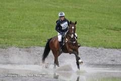 Rider 117 gallops a horse through water
