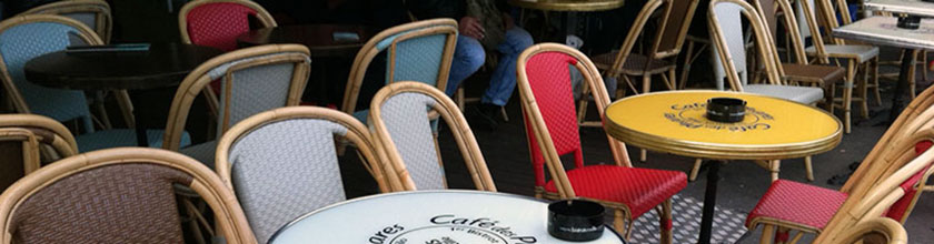Tables and colorful chairs at a French cafe.