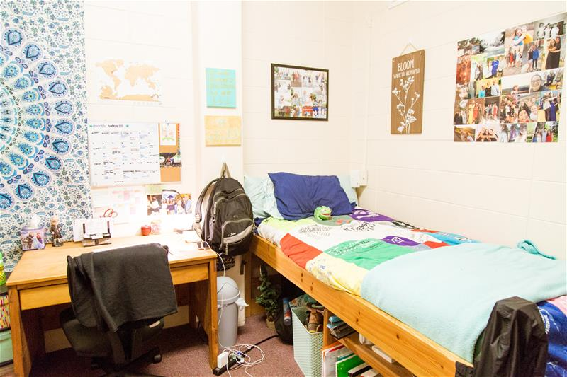 View of a bed closes to the window of the residential room in Moreland Residence Hall