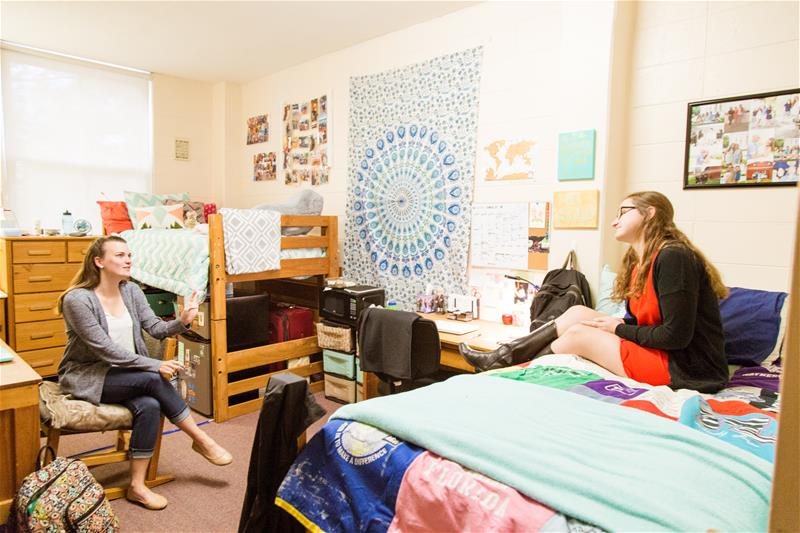 Front entrance view of the room with the students - one sitting on the bed and the other student sitting in the desk chair of the residential room in Moreland Residence Hall
