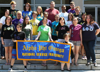 Students Standing Behind Alpha Phi Omega Banner