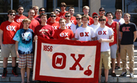 Students Standing Behind Theta Chi Banner