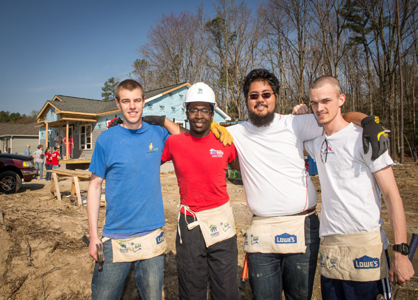Four Habitat 4 Humanity Students Resting Arms on Each Other's Shoulders